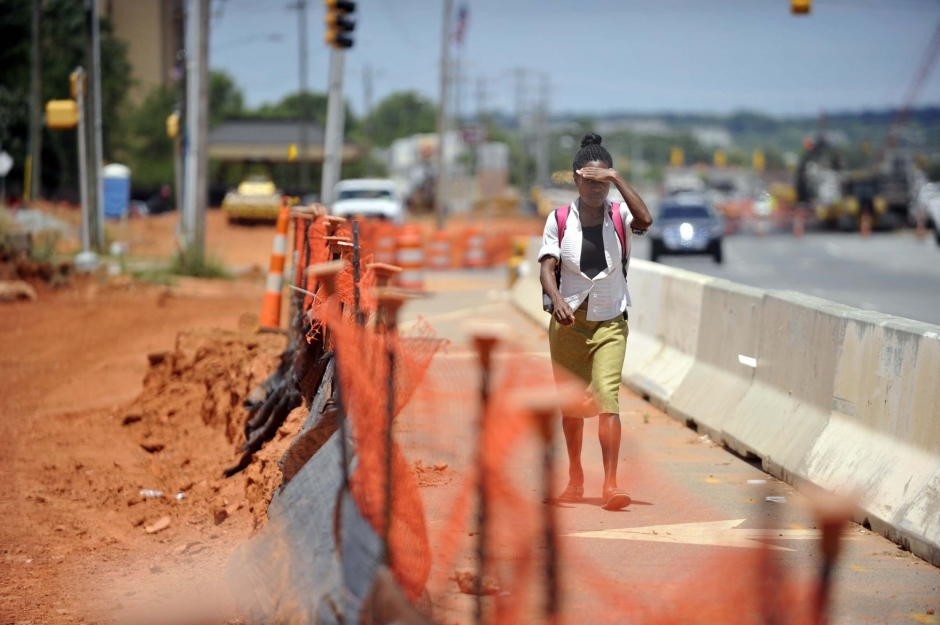 Pedestrian on temporary pedestrian path along North Tryon Street near University Pointe Boulevard. Photo: Nancy Pierce 6-11-15