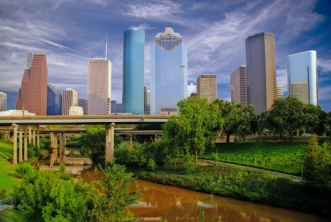 A muddy Buffalo Bayou flows near the downtown Houston skyline.