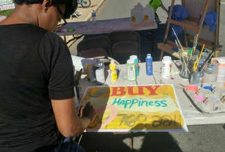 """Young woman Painting a sign that reads """"Can't Buy Happiness"""""""