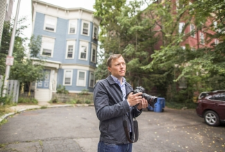 Author Matthew Desmond holds a camera in front of a house. Photo: John D. & Catherine T. MacArthur Foundation