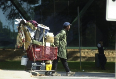 Man pulling shopping cart piled high with possessions