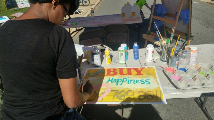 "Young woman Painting a sign that reads ""Can't Buy Happiness"""