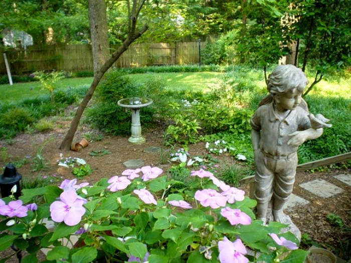 Flowers and a statue decorate Ernie McLaney's wildlife habitat garden