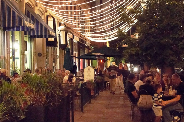 Sidewalk cafes with lights and trees in Denver's Restaurant Row.