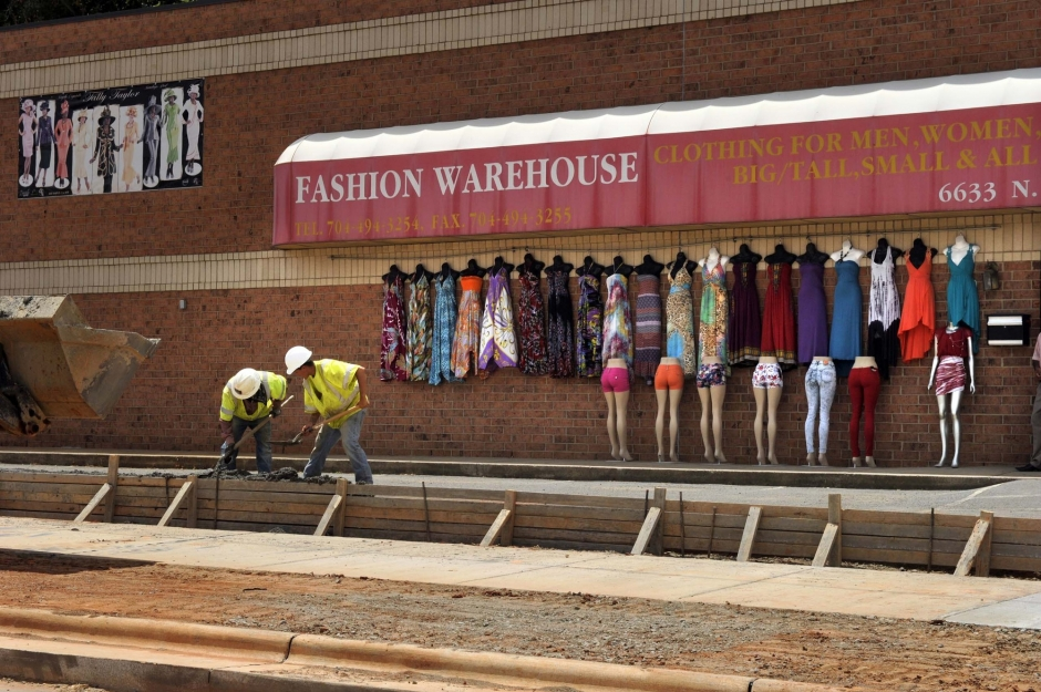 Crews work on a parking lane, curb, gutter and sidewalk in front of Fashion Warehouse, North Tryon Street at Tom Hunter Road. Photo: Nancy Pierce 6-11-15