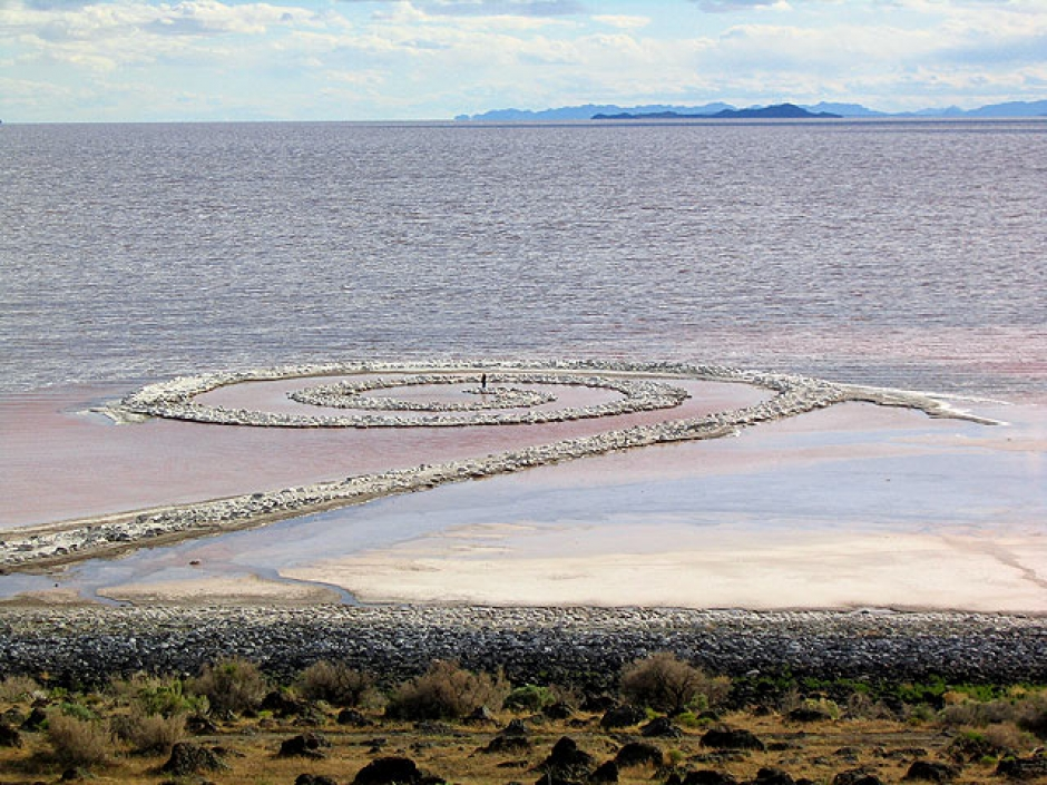 """A person standing in the middle of Robert Smithson's """"Spiral Jetty"""" on the Great Salt Lake in rural Utah. Photo: Wikipedia"""