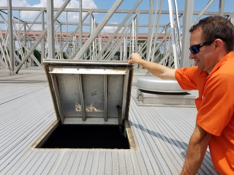 Charlotte Water project coordinator Will Rice lifts the hatch on a tank full of raw sewage water at the McAlpine Wastewater Treatment Plant.