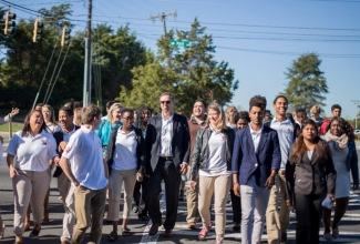 Gil Penalosa leads South Meck High School  students across Park Rd. where there is a  need for safe crosswalks connecting to the Southminster retirement facility . Photo: Juan Ossa.
