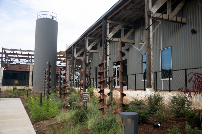 An old silo, restored wooden trusses, augers and native plants form some of the backdrop at Camp North End's Gama Goat building. Photo: Ely Portillo