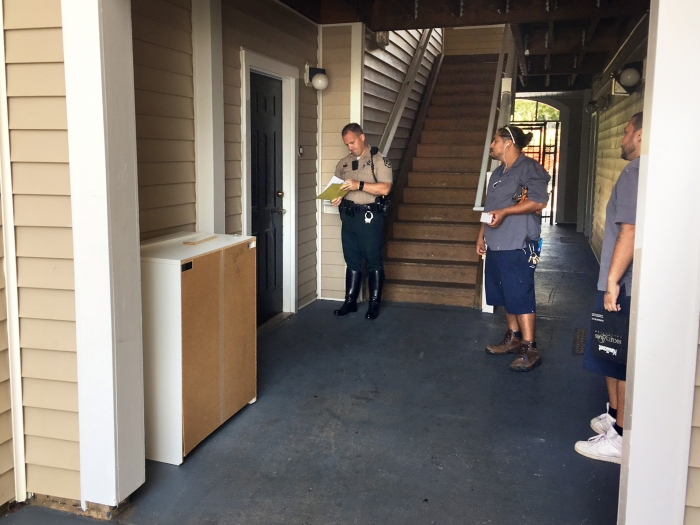 A sheriff's deputy stand outside an apartment. Photo: Mary Newsom